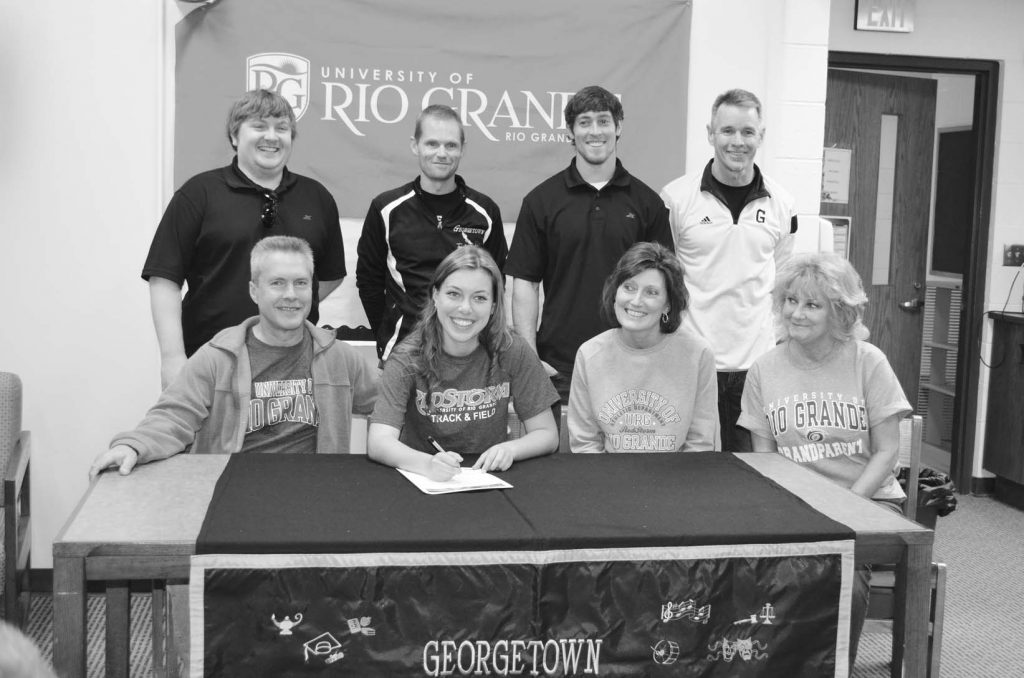 Georgetown senior Kelsey Miller signs her letter of intent to continue her running career at the collegiate level at Rio Grande University during a signing ceremony held April 15. Front row, from the left, are Kevin Miller (father), Kelsey Miller, Nina Miller (mother), and Sherry Goecke (grandmother); back row, Rio Grande assistant coach Jordan Cunningham, Georgetown High School cross country and track coach Tony Watson, Rio Grande assistant coach Craig Dougherty, and Georgetown Jr./Sr. High School Principal Jerry Underwood.  Photo by Wade Linville.